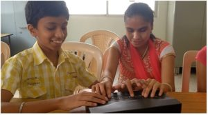 A picture of Chetan and Afya, two of our younger testers of Touché, at Jyothi Seva School for the Blind.